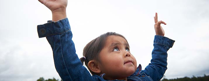 child with hands raised