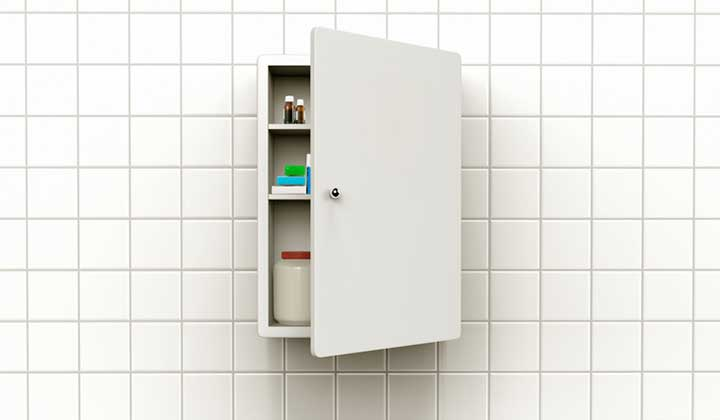 Medicine cabinet with mirrored door partially open, white cabinet, white tile wall