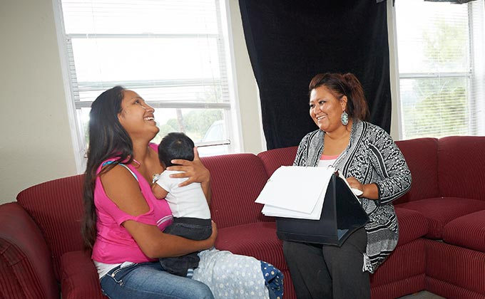 happy mom with child, visited by a social worker