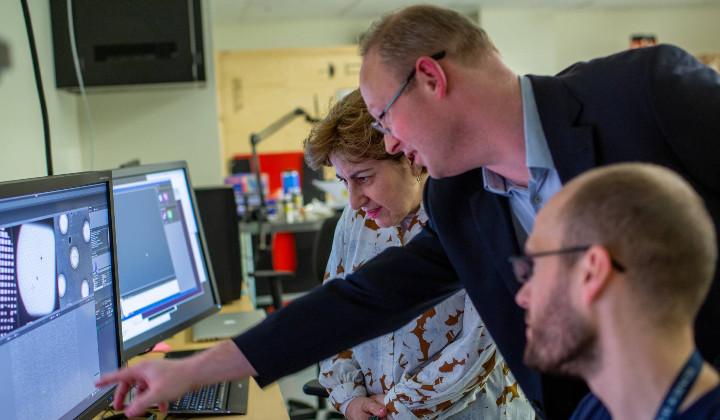 Three people face a desk with a pair of computer monitors on the left. Associate Professor Scott Bailey leans forward, reaching to point at the computer screen. Behind him to the left, Elizabeth Walder stands, looking down at section of the screen that Bailey is pointing at. On the right, in front of Bailey, postdoctoral fellow Evan Worden sits, head turned toward the screen.