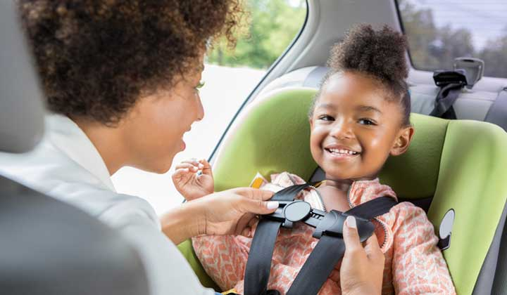 child getting buckled into car seat by mom