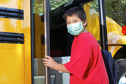 Kid getting on bus with mask