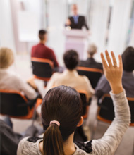 Student raising her hand at a lecture hall
