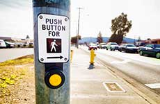 Pedestrian crosswalk button next to busy street