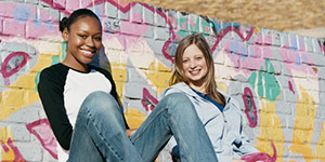 Two girls posing on a colorful brick wall