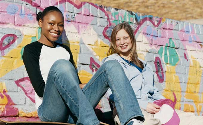 Two girls sitting in front of a painted mural wall