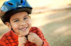 young boy putting on his bike helmet, smiling