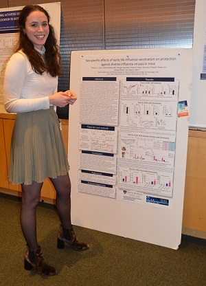 Photo of poster competition winner standing in front of her poster smiling